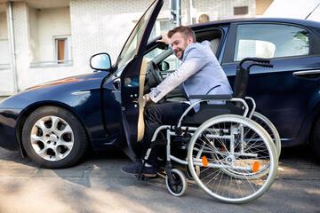 Rollstuhlfahrer mit Auto